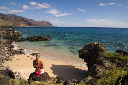 Blond girl sit at beach cove in hawaii staring at turquoise sea photo