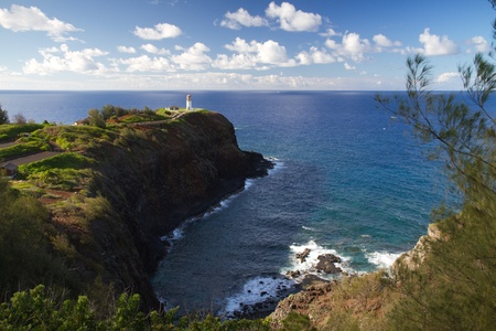 Kilauea lighthouse northern guide in Kauai island and underlying cove with calm ocean in background