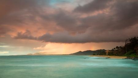 squall: Colorful Kauai coastline during a morning thunderstorm at sunrise