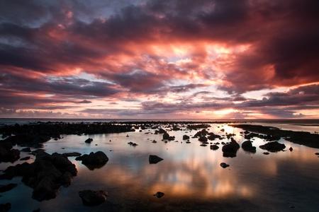 Mooie zonsondergang scene in Kauai, Hawaii. Met verspreid lava rotsen en dramatische wolkenlucht