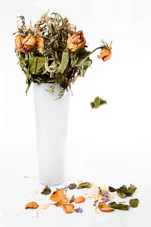 Vase of dried roses with falling leaves and petals photo