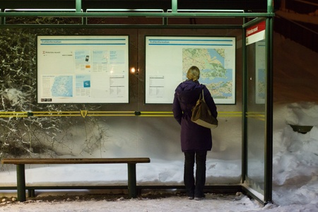Blond girl looking for directions at bus stop in Stockholm during night time Stock Photo