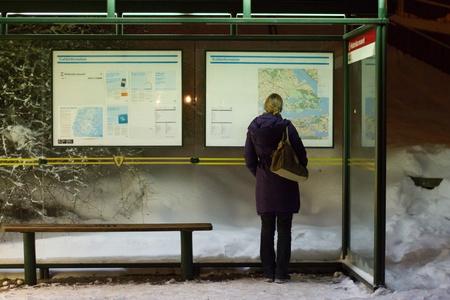 Jeune fille blonde à la recherche de sens à l'arrêt de bus à Stockholm pendant la nuit