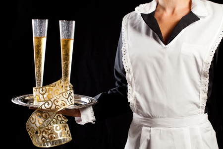 Young maid in uniform serving two glasses of champagne with tray and festive gold decorations photo