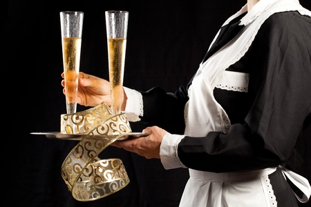Young waitress in uniform serving two glasses of champagne with tray and festive gold decorations photo