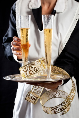 Young maid in uniform serving two glasses of champagne with tray and festive gold decorations. Against black background photo