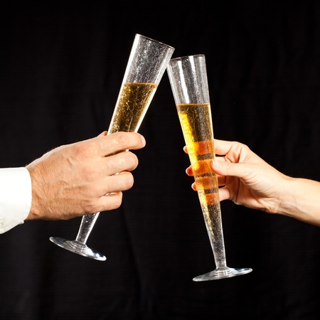 gold flute: male and female hands holding glass of champagne and tossing against black background