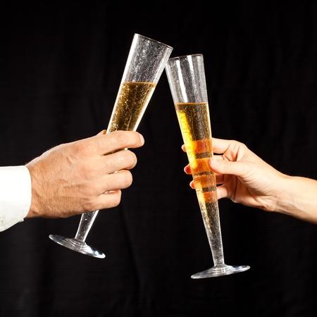 brindisi champagne: mani degli uomini e donne in possesso di un bicchiere di champagne e lanciando contro sfondo nero
