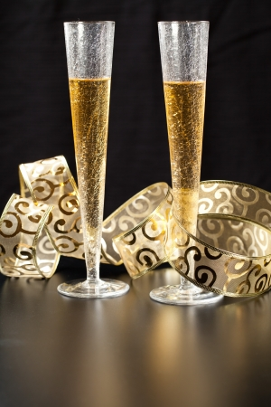 Two stylish glass of champagne with gold festive decorations against black background photo