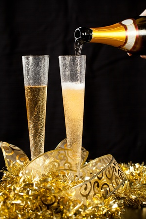 gold flute: Pouring champagne in two crystal glasses with festive gold decorations and black background