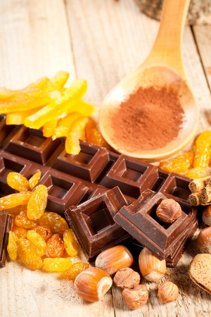 Chocolate bar and chunks with cocoa powder, dried fruit and assorted nuts over a wooden table photo