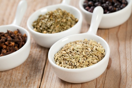 Fennel seeds and ssorted dry herbs and spices in white bowls over a wooden table photo