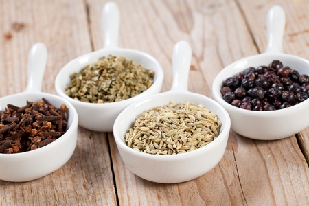 Assorted dry herbs and spices in white bowls over a wooden table photo