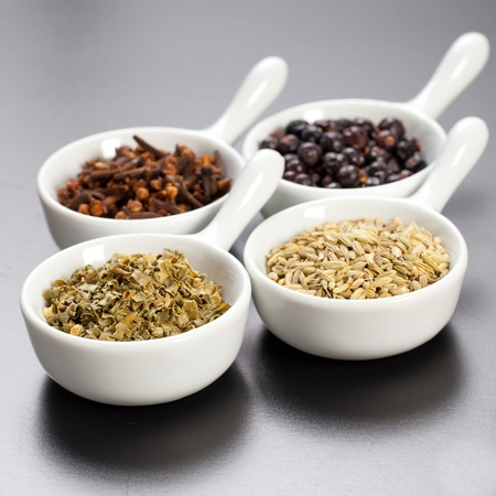 Assorted dry herbs and spices in white bowls over a black board photo