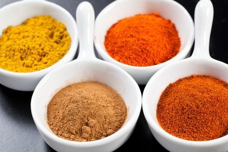 Assorted hot spicy powders in white bowls over black table photo