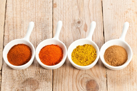 Assorted hot spicy powders in white bowls over wooden table