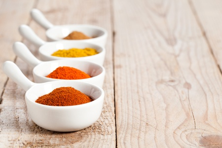 Assorted hot spicy powders in white bowls over wooden table photo