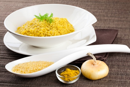 Dish of cooked saffron and curry rice with raw ingredient on side over a brown tablecloth photo