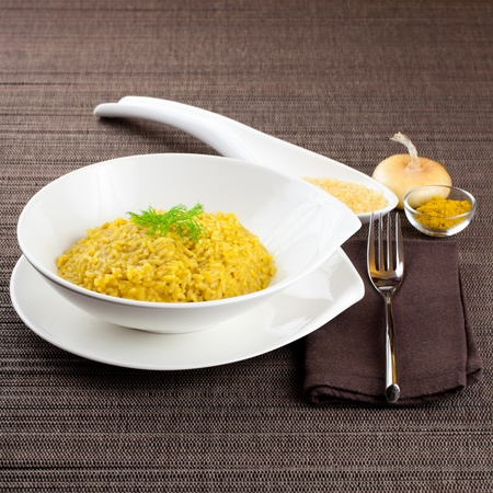 Dish of cooked saffron and curry rice with raw ingredient on side over a brown tablecloth Stock Photo