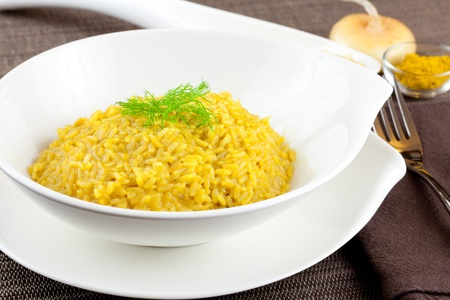 Dish of cooked saffron and curry rice with raw ingredient on side over a brown tablecloth Archivio Fotografico