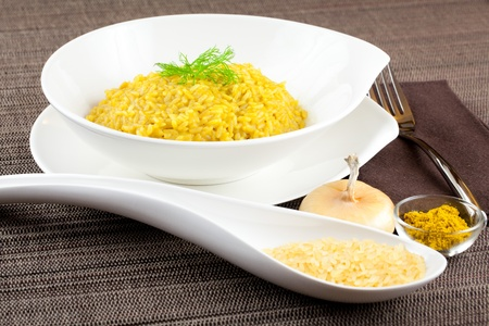 Dish of cooked saffron and curry rice with raw ingredient on side over a brown tablecloth Stock Photo - 11550975