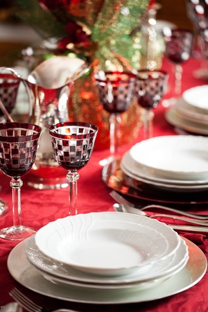 Elegant place setting with white dishes over a red table cloth plus goblet and decorations