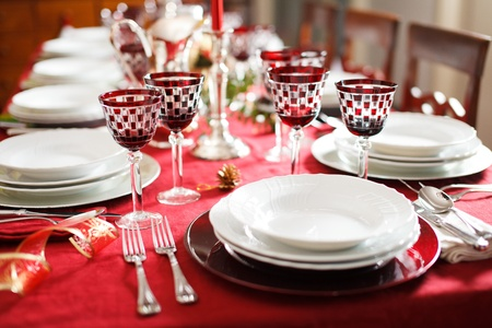 Elegant and decorated table setting with white dishes over a red tablecloth. Silver cutlery and red glasses