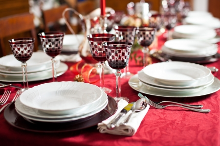 dinnerware: Banquet with red table setting. Red tablecloth, white dishes, silver cutlery and red checked goblet glasses plus some decorations Stock Photo