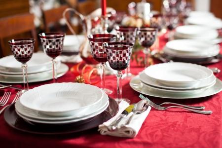 cena navide�a: Banquete con el ajuste de la tabla de color rojo. Mantel rojo, platos blancos, cubiertos de plata y rojo controladas vasos caliciformes, m�s algunos adornos