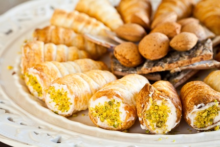 Plate of puff pastry rolls with ham cream and minced pistachios, decorated with pine wood and almonds photo
