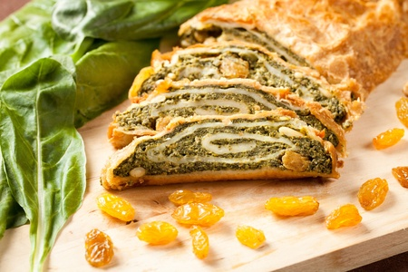 pasty: Traditional vegetables strudel pie, homemade and sliced over a wooden board and decorated with raisins and nuts