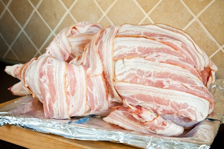 uncooked bacon: Uncooked stuffed turkey covered with bacon ready to be cooked over an oven plate Stock Photo