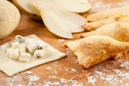 Triangle wraps of puff pastry with blue cheese and pear. Baked, fresh and surrounded with raw ingredients