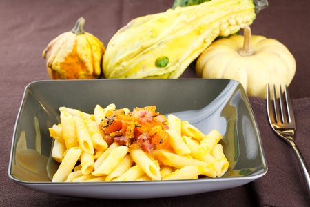 Pasta with pumpkin and bacon served in an elegant green dish, decorated with rosemary and surrounded with assorted mini pumpkins on a brown tablecloth photo