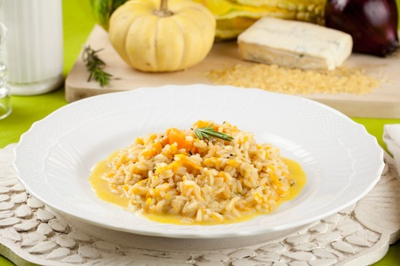 Rice with pumpkin and gorgonzola cheese in elegant dishware and raw ingredient in background Stock Photo - 11988568