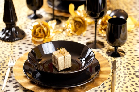 Golden gift box in a black and gold table setting with gold roses over a leopard tablecloth