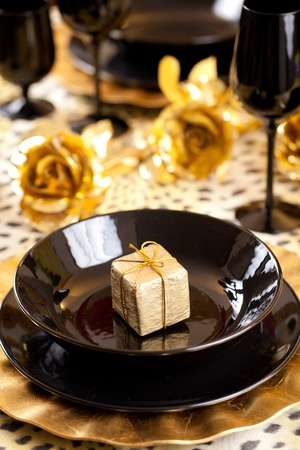 Golden gift box in a black and gold table setting with gold roses over a leopard tablecloth photo