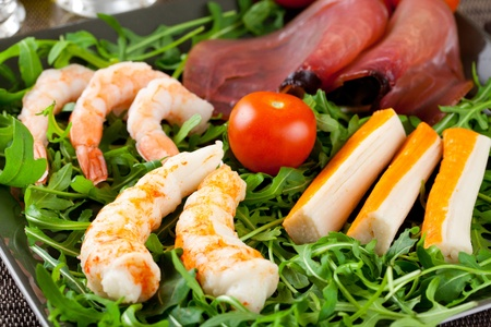 Tuna carpaccio, prawns, shrimps, lobster and crab surimi over a bed of arugula salad in a modern dish and place setting