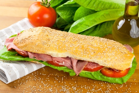 Sesame baguette sandwich with lettuce, tomato and roast beef with raw ingredients in background photo