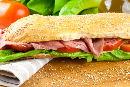 Sesame baguette sandwich with lettuce, tomato and roast beef with raw ingredients in background