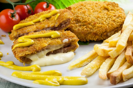 Delicious cordon bleu with melting cheese and french fries. Garnished with mustard, tomatoes and lettuce Stock Photo