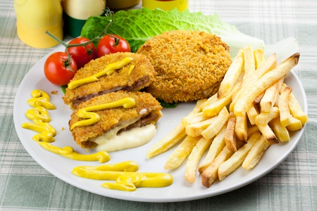 cordon: Delicious cordon bleu with melting cheese and french fries. Garnished with mustard, tomatoes and lettuce Stock Photo