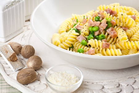 Delicious fusilli pasta with ham bits and green peas, garnished with parmesan cheese and nutmeg. Served in a white place setting Stock Photo