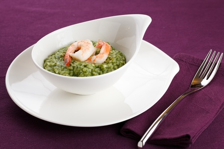 Delicious rice with spinach, greens and shrimps. Served in a modern dishware over a violet table setting photo