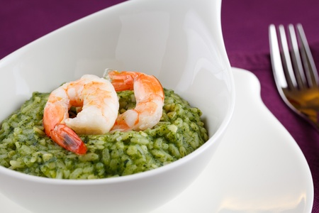 Delicious rice with spinach, greens and shrimps. Served in a modern dishware over a purple table setting