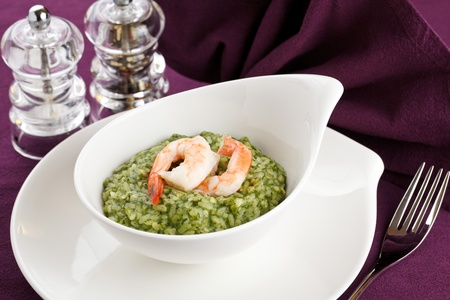 Delicious risotto with spinach, greens and prawns. Served in a modern dishware over a purple table setting photo