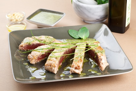 Delicious tuna steak with mint sauce. Sliced and decorated with chive and mint leafs. Served in a trendy green dishware Stock Photo