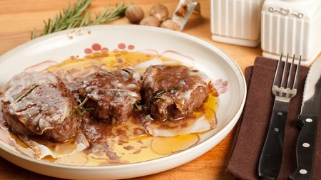 Filet mignon wrapped in bacon and cooked in red wine sauce. Served in porcelain dish with a nutmeg dusting finish Stock Photo