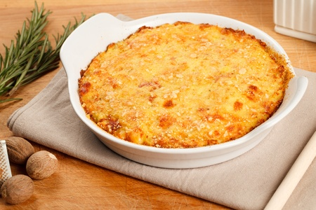 Traditional gateau potatoes pie with cheese and nutmeg. Served in a terrine over a wooden board Archivio Fotografico