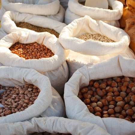 Jute bags full of beans and nuts in a market stall photo